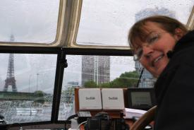 Nuala steering the boat past the Eiffel Tower in the rain